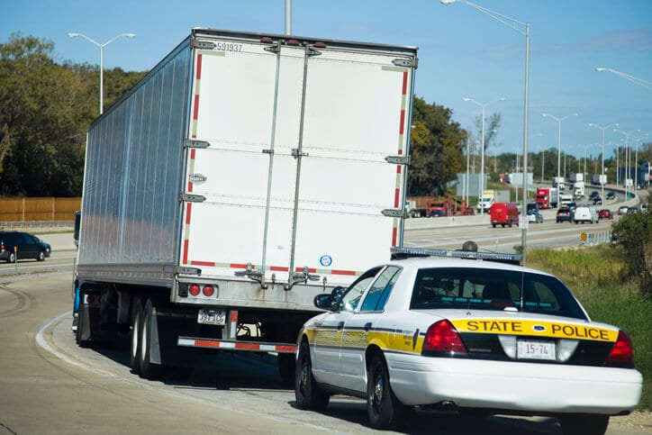 A police car sits behind a laege white truck during ELD inspection