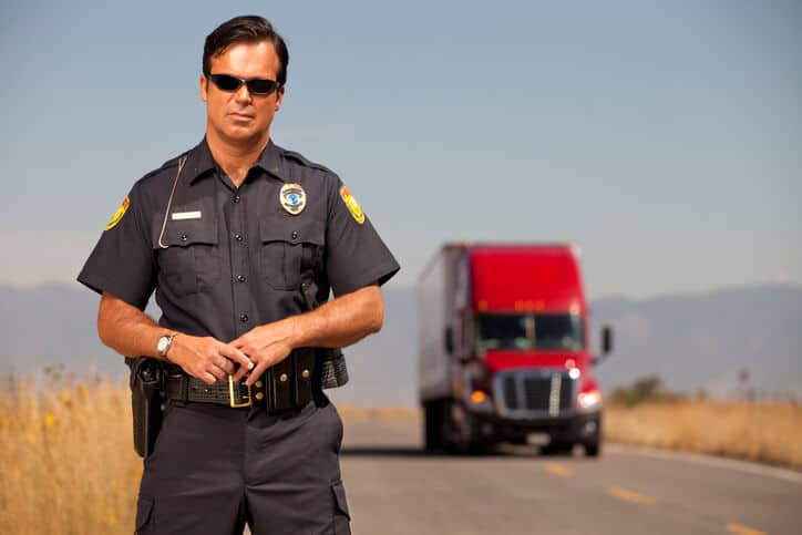 police officer in front of a red truck on a wide open road