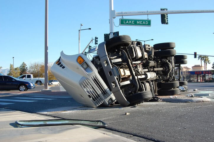a bad truck crash that left a white truck badly damaged and on its side