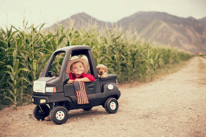 A little boy sits in a toy truck in a field with his dog in the back