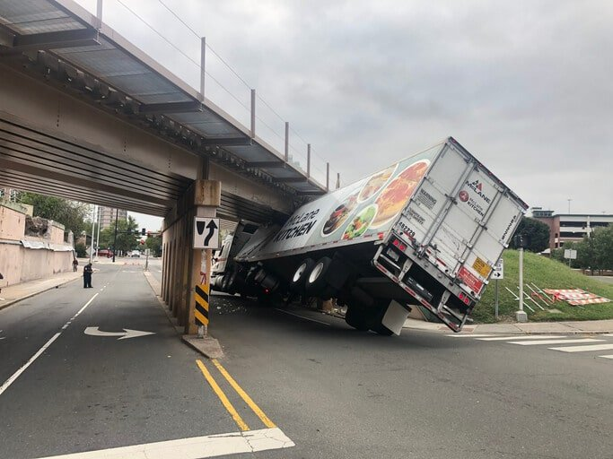 a semi truck carrying food is caught under a bridge that was too small to travel under