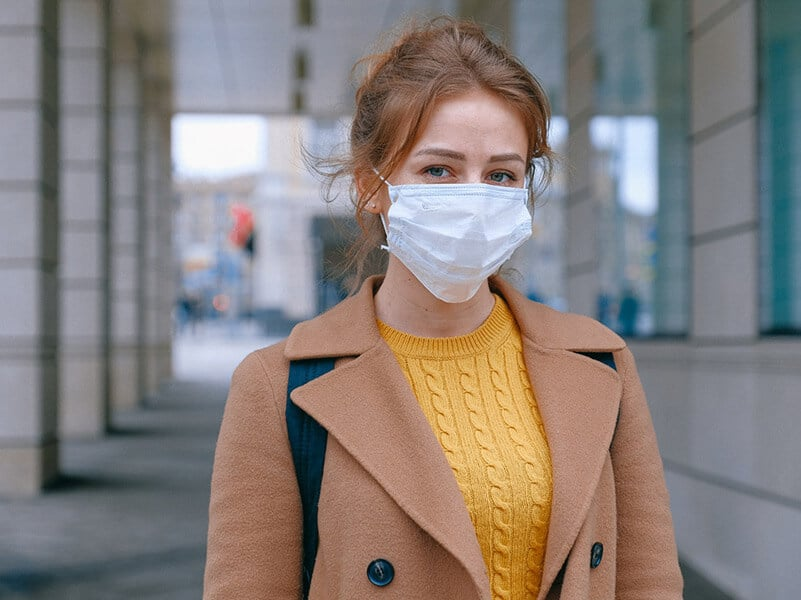 a woman in a tan jacket and yellow sweater wears a face mask