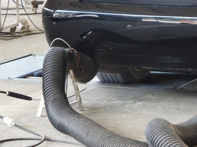 a government fleet vehicle gets a smog emissions test in a garage