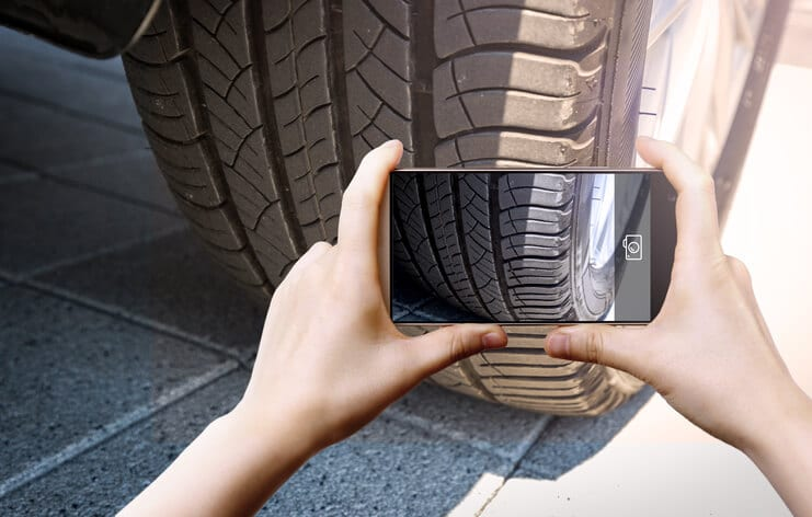 A fleet driver takes a photo of a tire with a cellphone camera for a DVIR